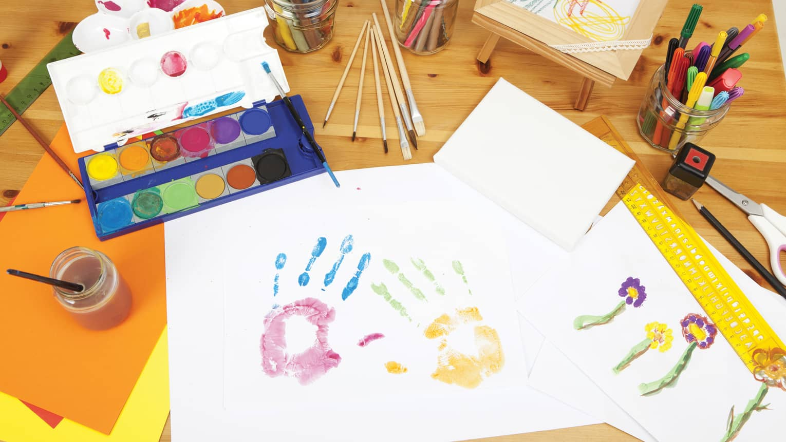 Two colourful paint handprints on paper next to tray of kid's paints on Kids Club craft table