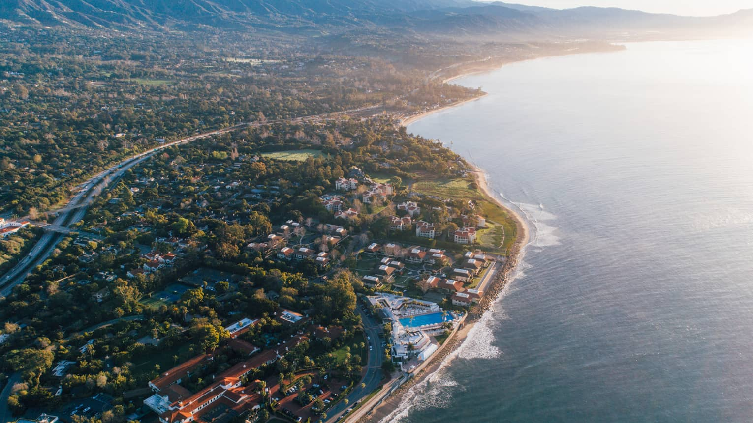 Aerial view of Santa Barbara coastline, trees and winding highways at sunset