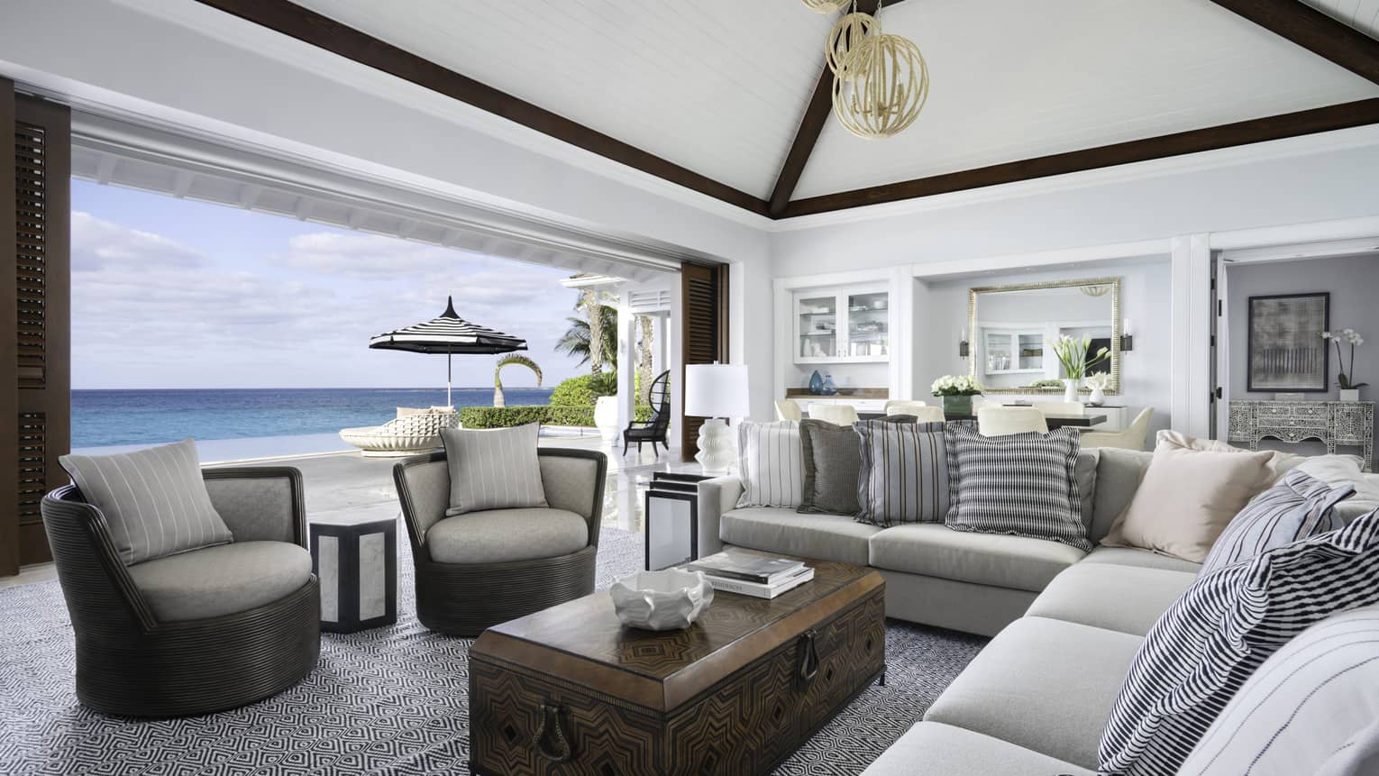 Beachfront Villa Residence large living room with modular sofa, armchairs by open wall to patio overlooking ocean