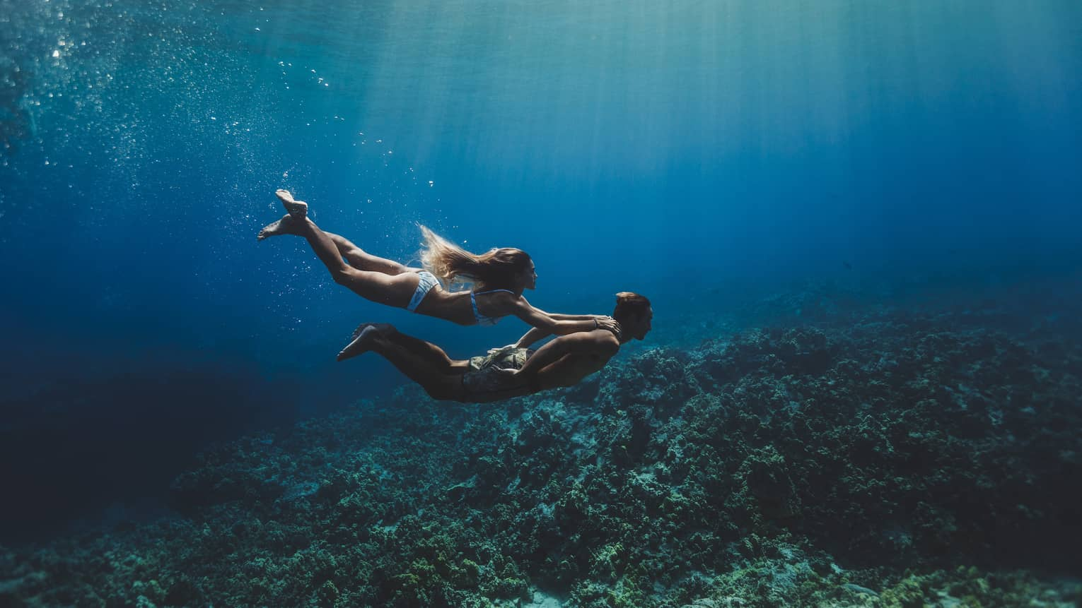 A man and woman swim underwater in the ocean over a coral reef.