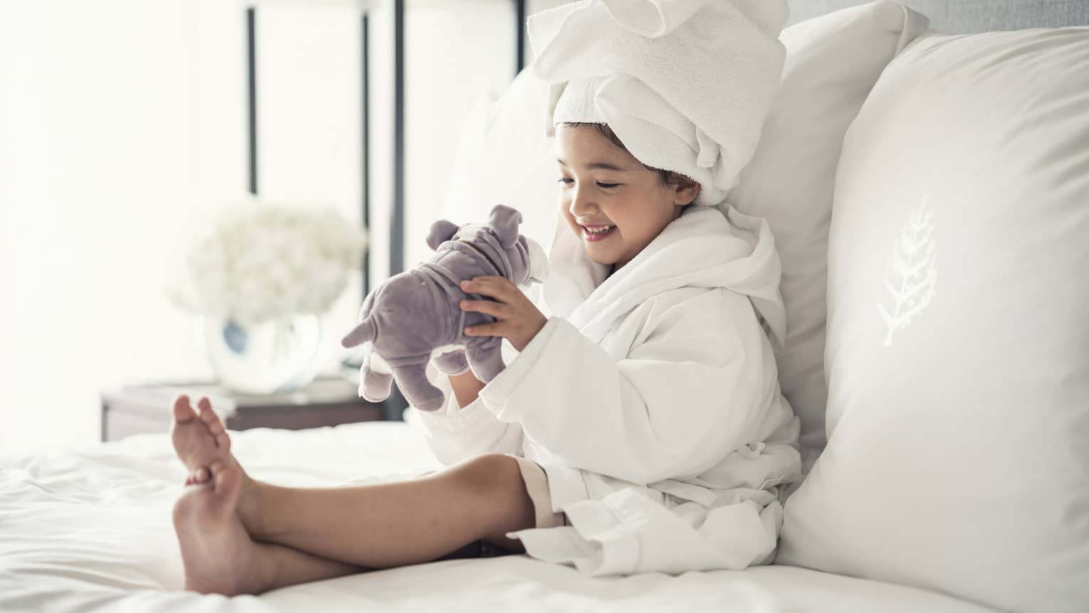 Young girl wearing a white bathrobe with towel wrap plays with plush dog toy on bed