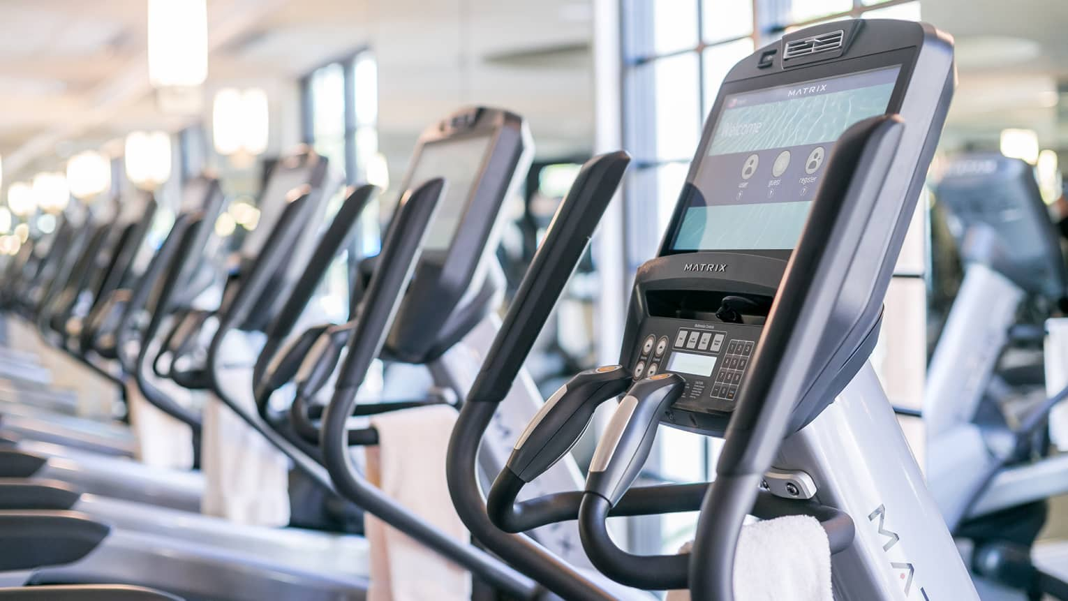Close-up of cardio elliptical machines in a row in fitness facility