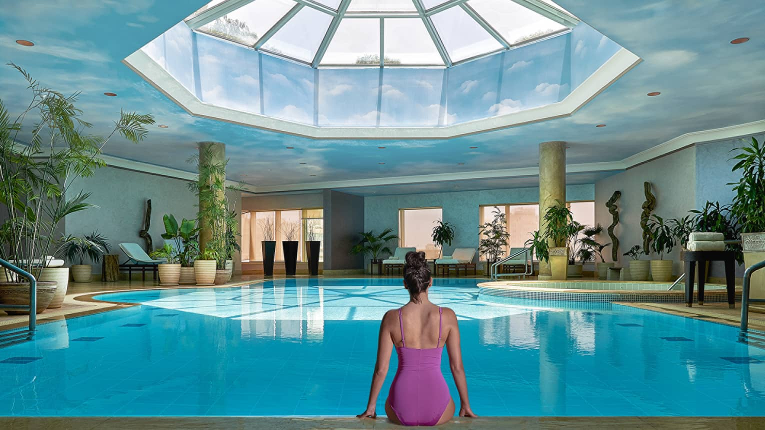 Woman in swimsuit seated on edge of indoor pool with blue ceiling and skylight above