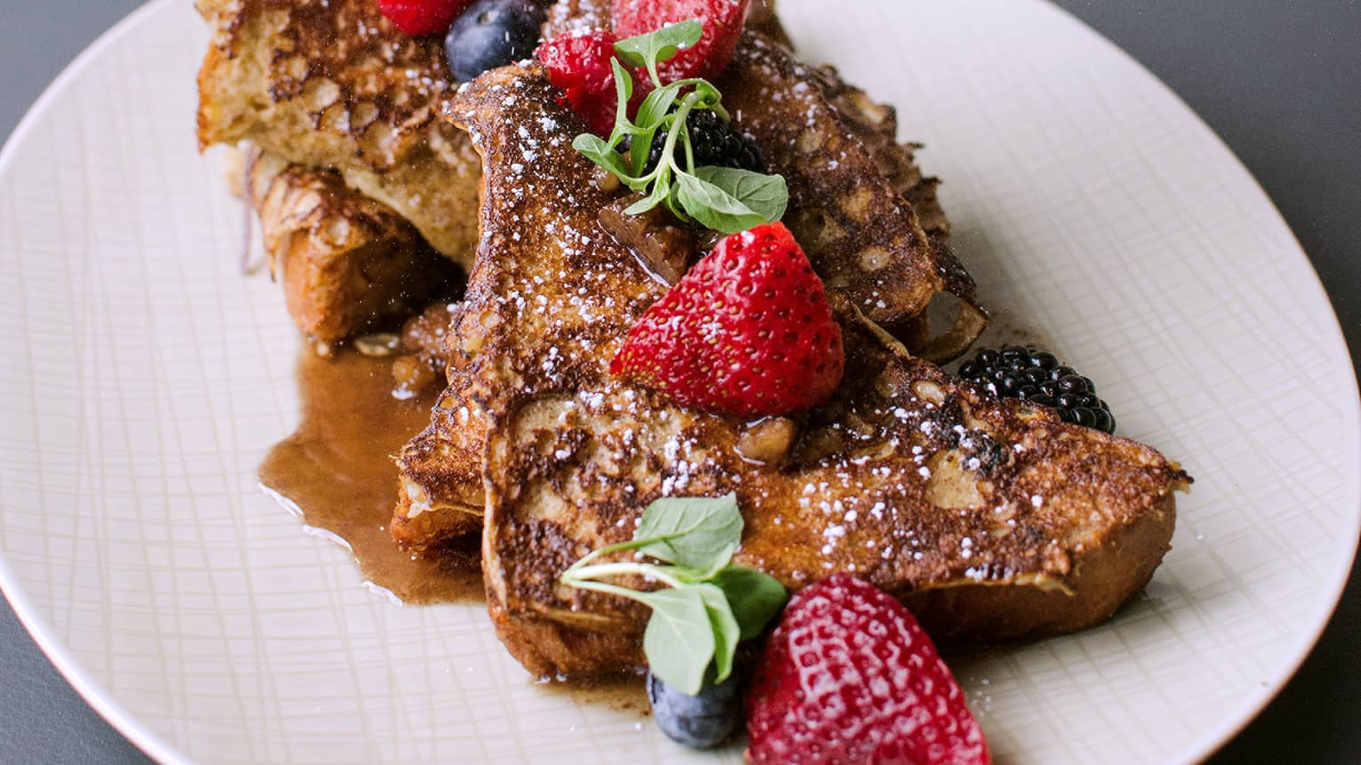 French toast topped with fresh berries, greens, syrup on white plate