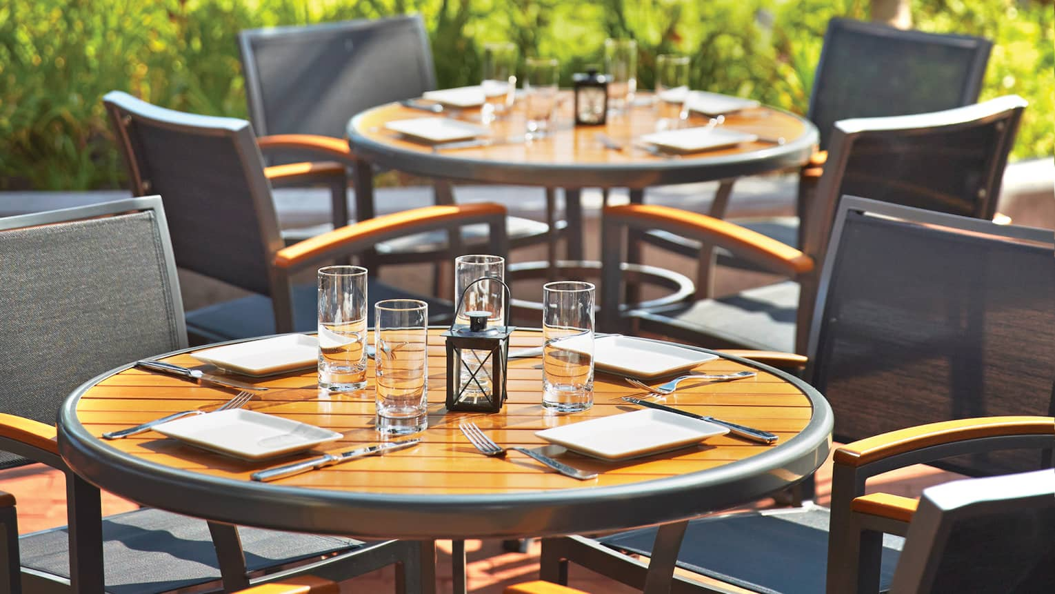 Round patio tables set with plates, glasses, lanterns on sunny day
