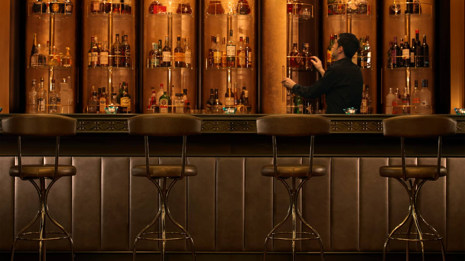Bentleys dimly-lit lounge, four stools at padded leather bar where bartender looks at racks of bottles on wall