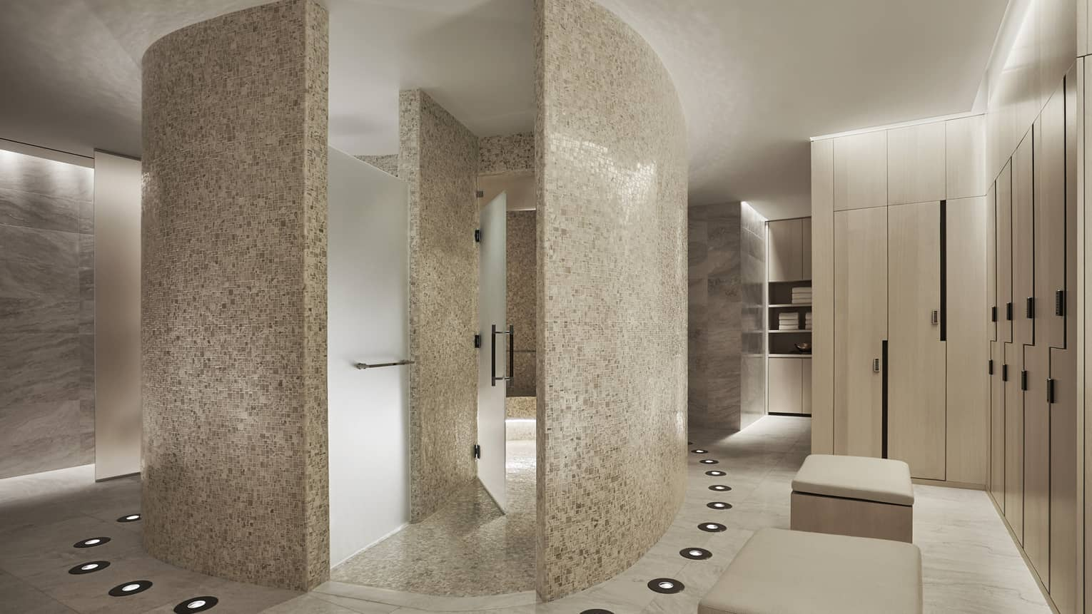 Curved white stone walls in Spa locker room, wood lockers