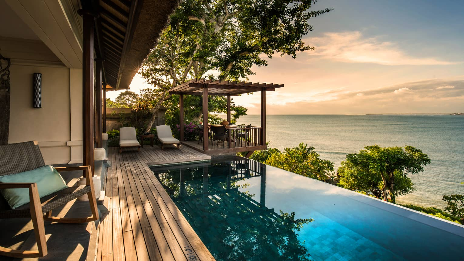 Private Ocean Villa patio at sunset with infinity swimming pool reflecting trees, clouds, white lounge chairs on side