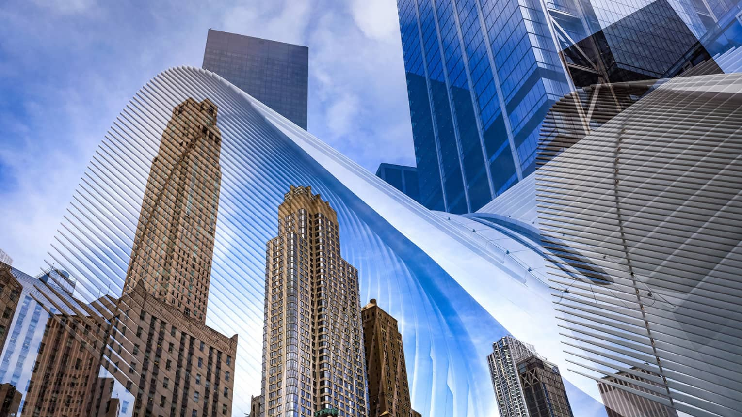 New York City skyline view behind architectural details of The Oculus train station terminal