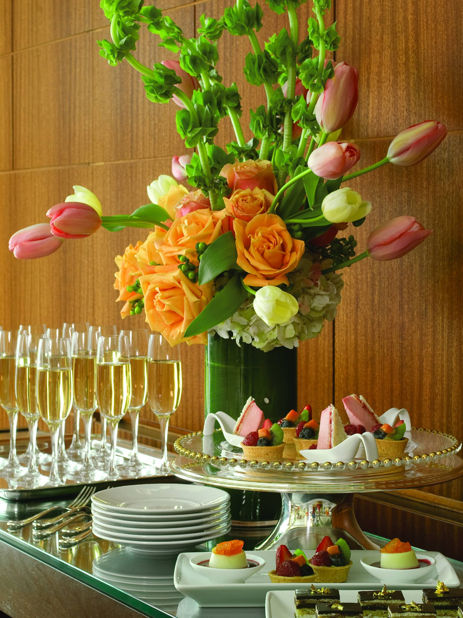 Intricate pastries, cakes and chocolates are arranged on a table next to a flower arrangement and champagne