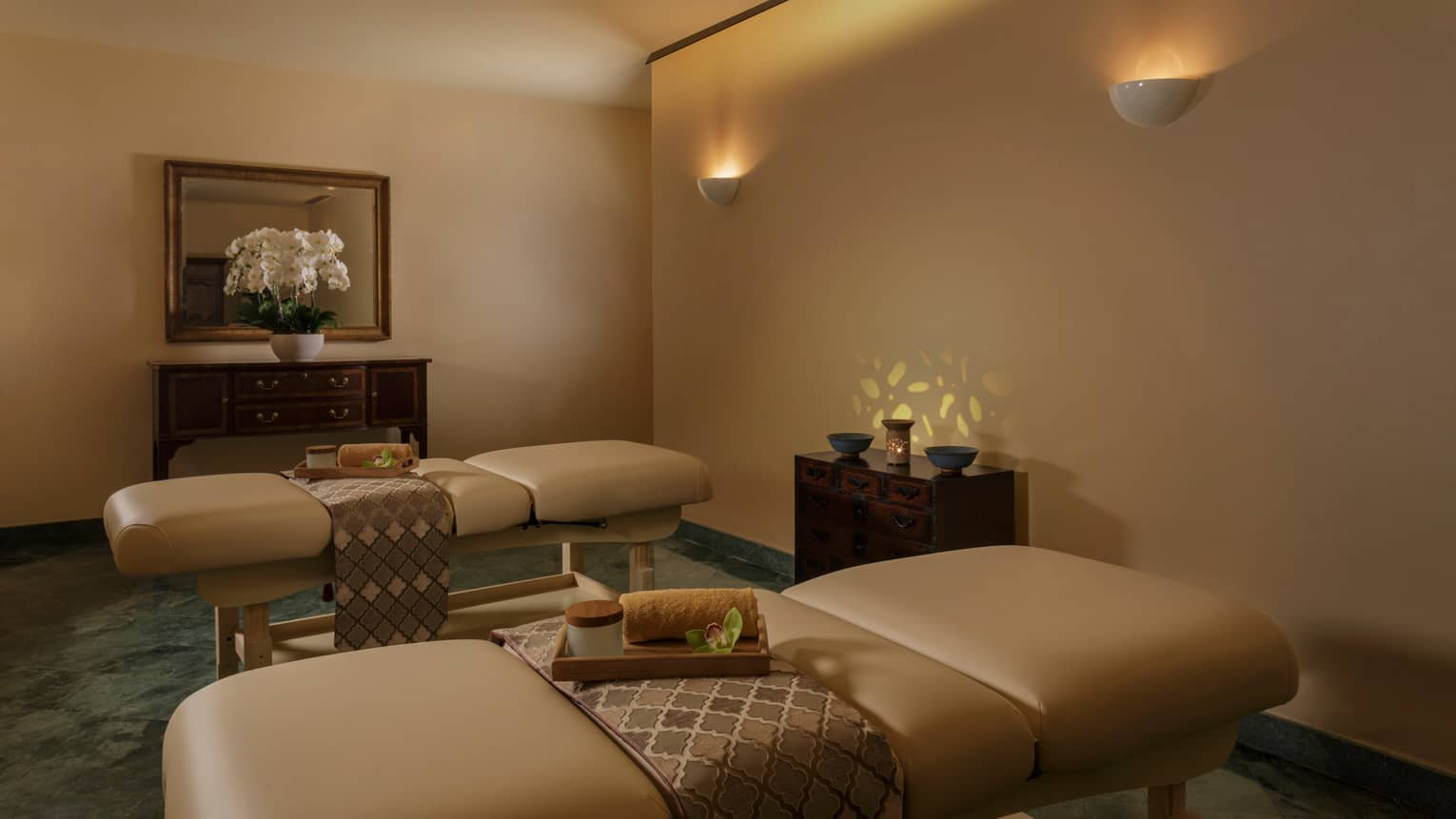 Two couple's massage beds with silk sashes, bamboo trays in dimly-lit spa room