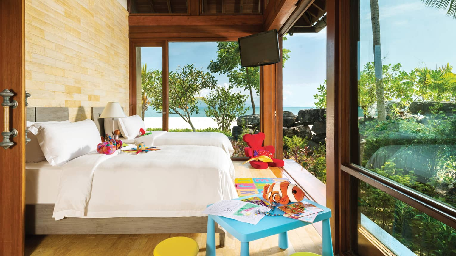 Family Beach Villa bedroom, double beds with child's toys, craft table, red bear chair