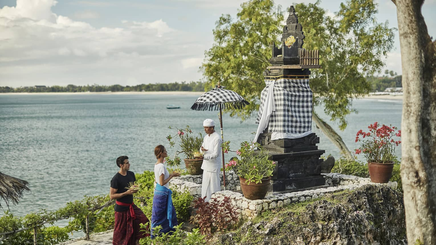 High Priest Aji Ngurah stands by shrine with black-and-white checkered umbrella, cloth, as man and woman make offering