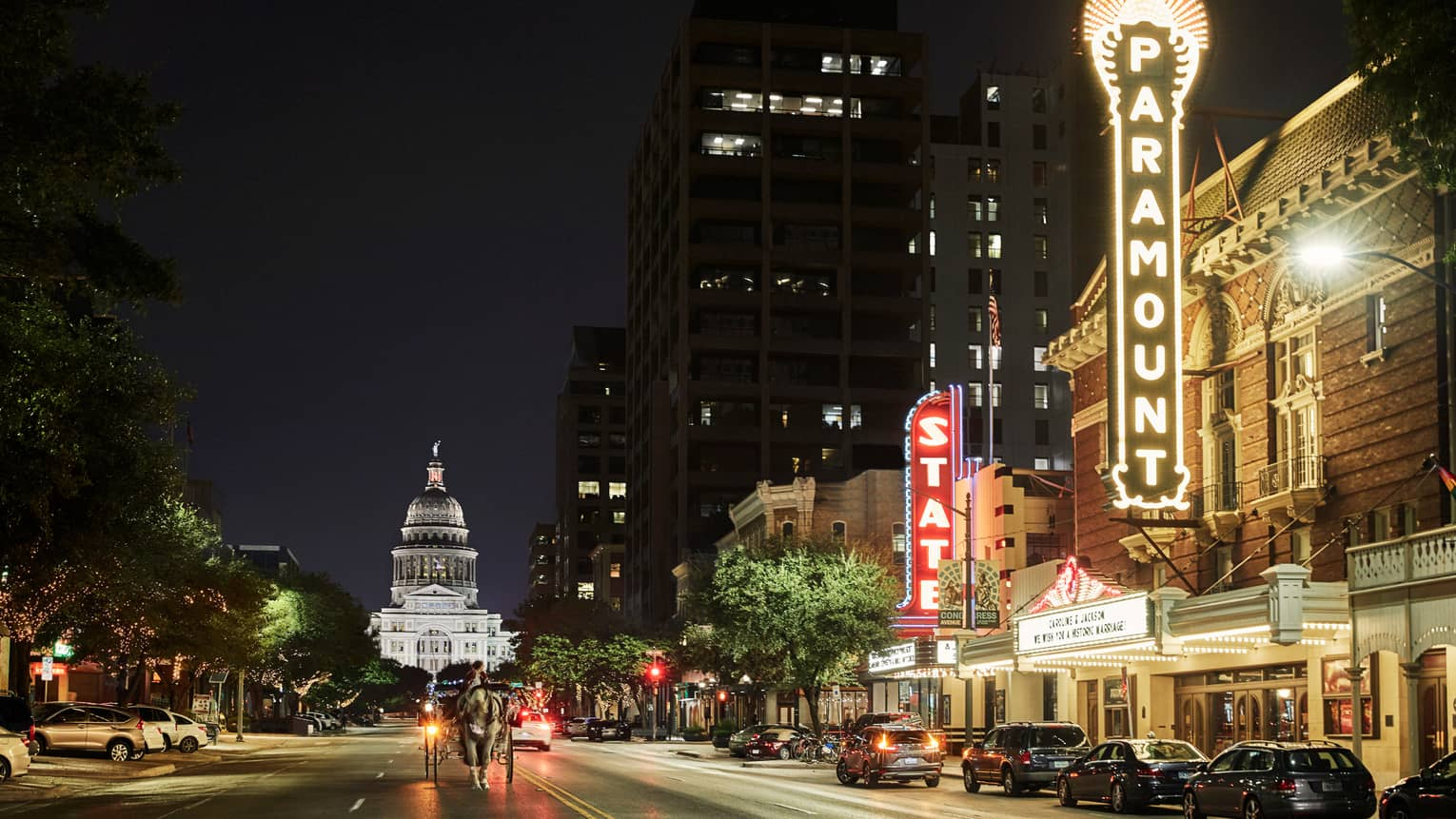 Horse, buggy in front of Texas State Capitol building, Paramount Theatre lights at night