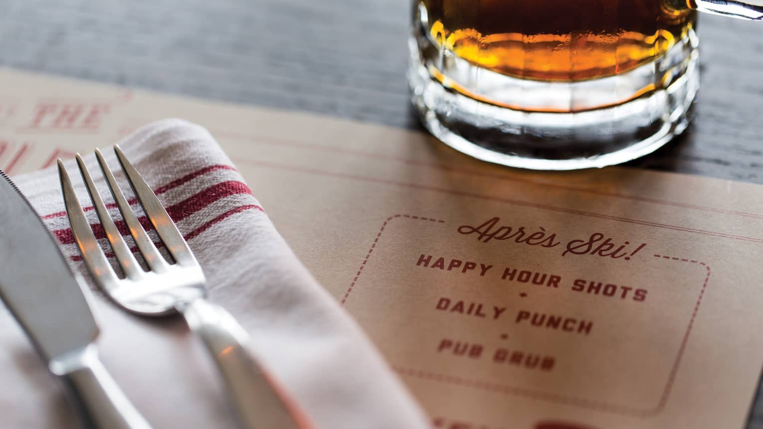 Close-up of knife and fork on napkin on menu near glass with liquor