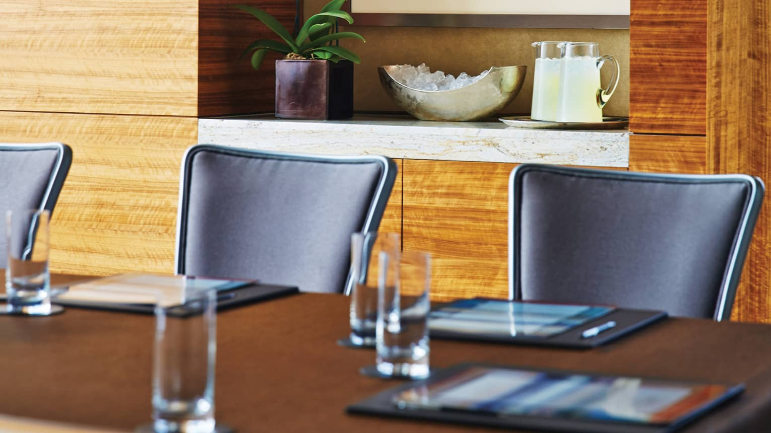 Boardroom table and black meeting chairs in front of modern wood wall, shelf with plant and jugs