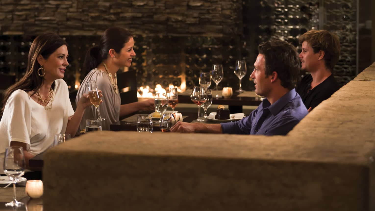 Couples drink wine at dimly-lit Terra restaurant dining tables by fireplace