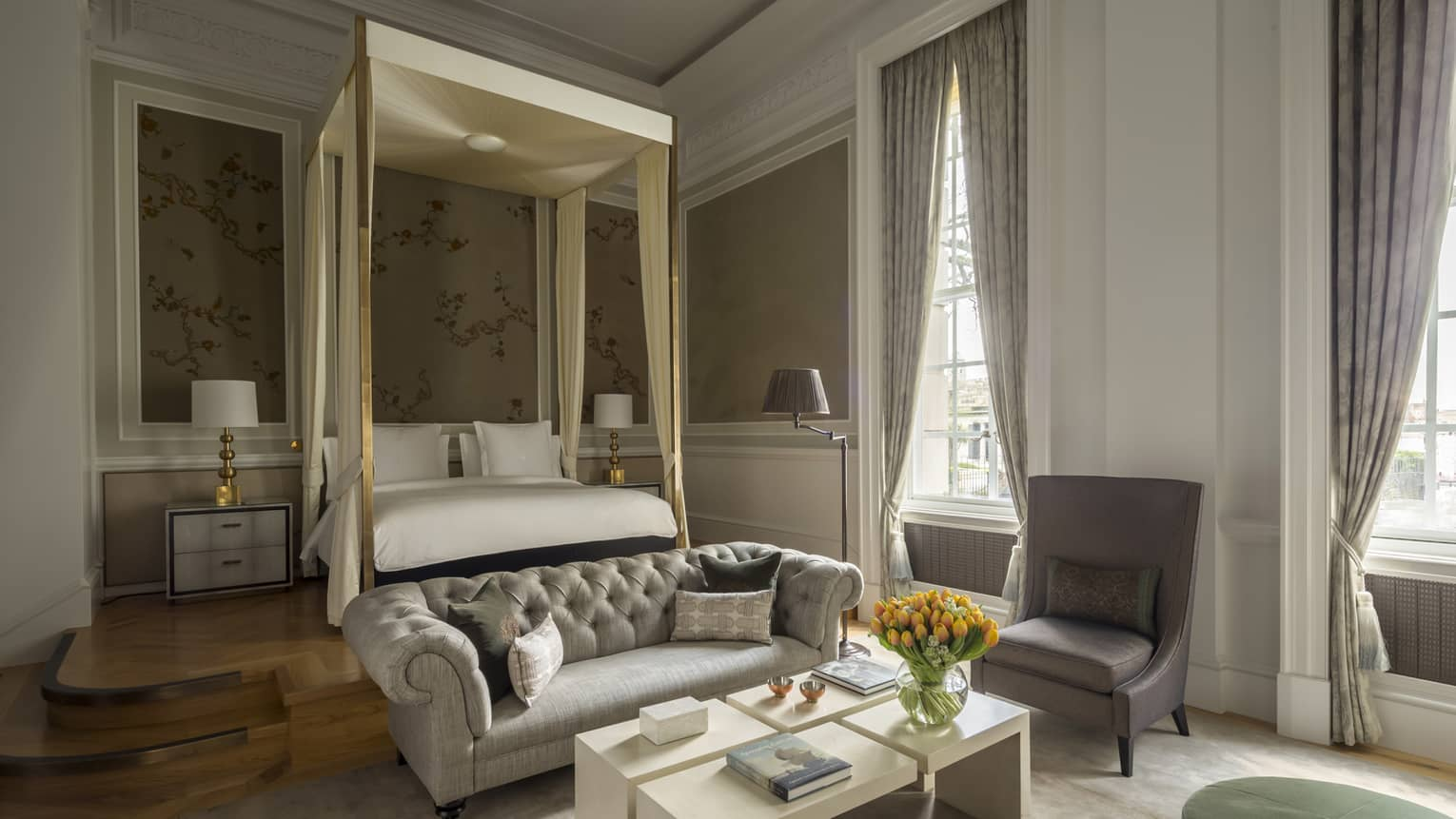 Heritage Suite with tall windows, canopy bed, tufted loveseat sofa, armchair and table at foot