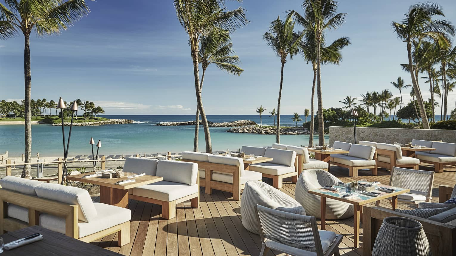 Plush white patio chairs around wood tables on sunny waterside Minas lounge
