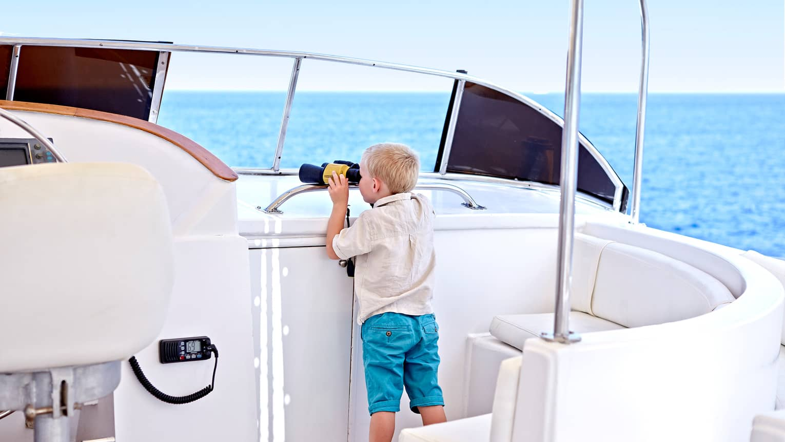 Young boy looks through binoculars on deck of white yacht