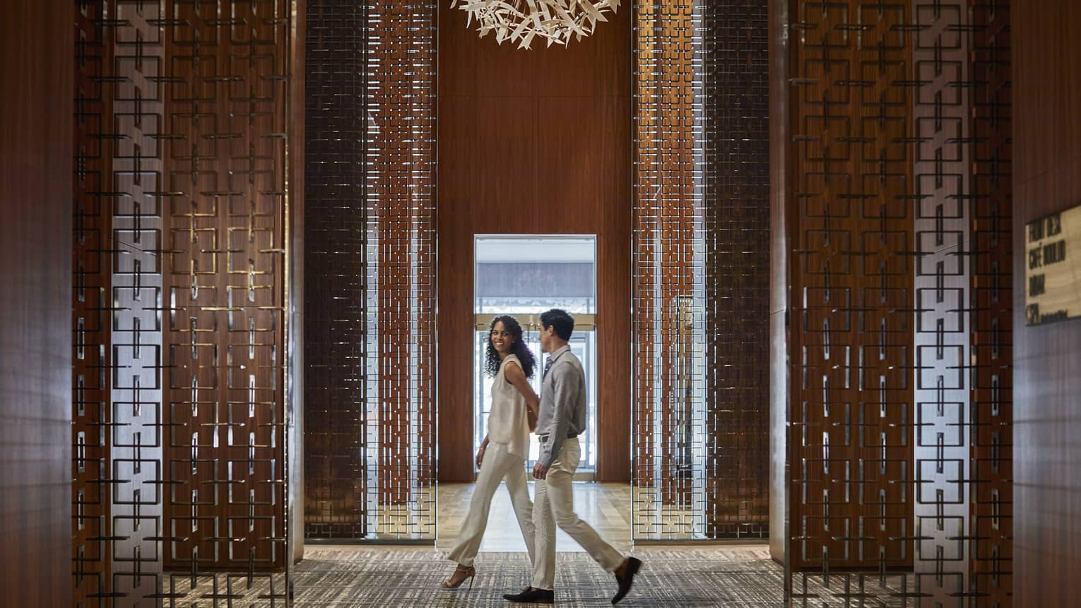 Couple walk through lobby with decorative wood panel walls, modern chandelier