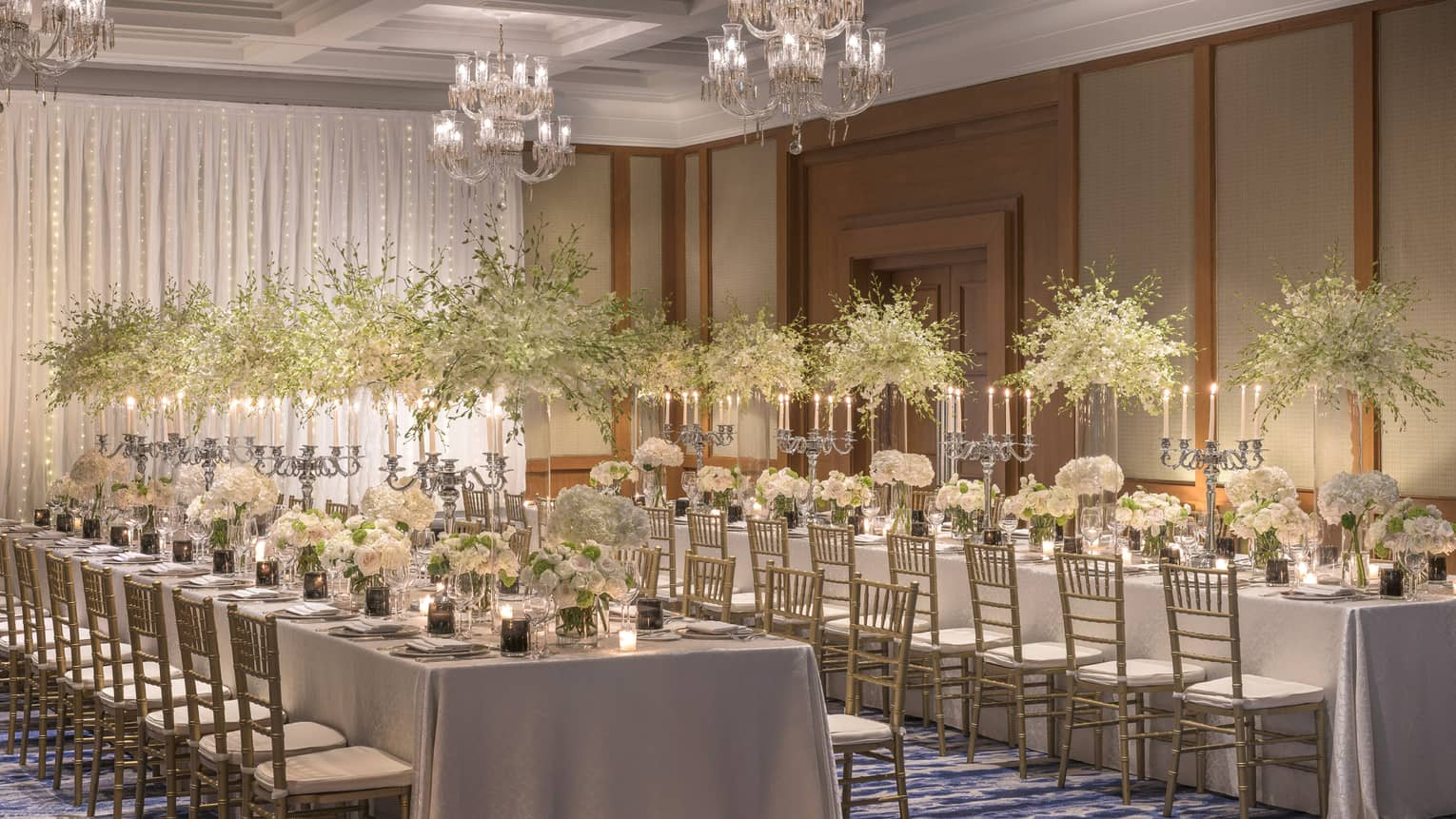 Two long tables are adorned with candelabras and tall and short bouquets of white flowers