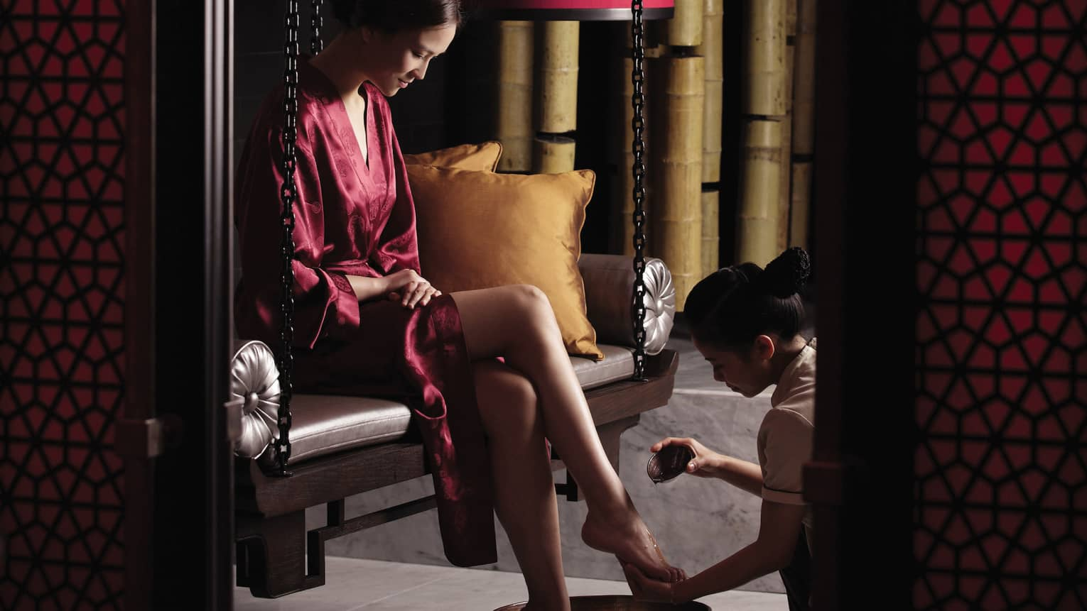 Woman in red silk robe sits on bench as Tranquil Spa staff pours oil on foot