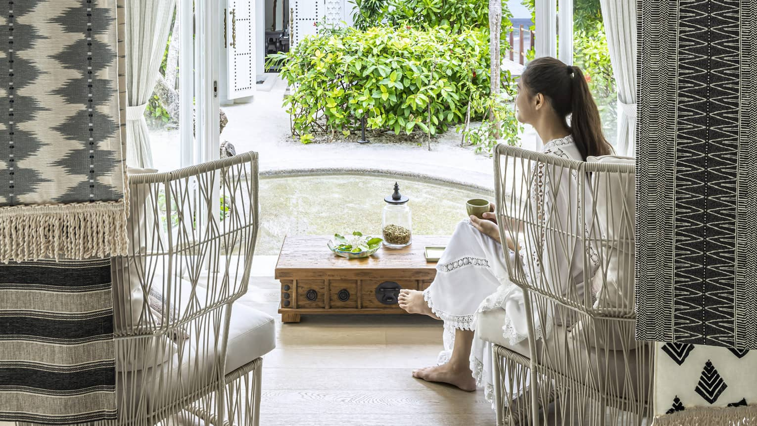 A woman sits in white wicker chair in the four seasons maldives spa waiting area and overlooks the garden outside an opened window