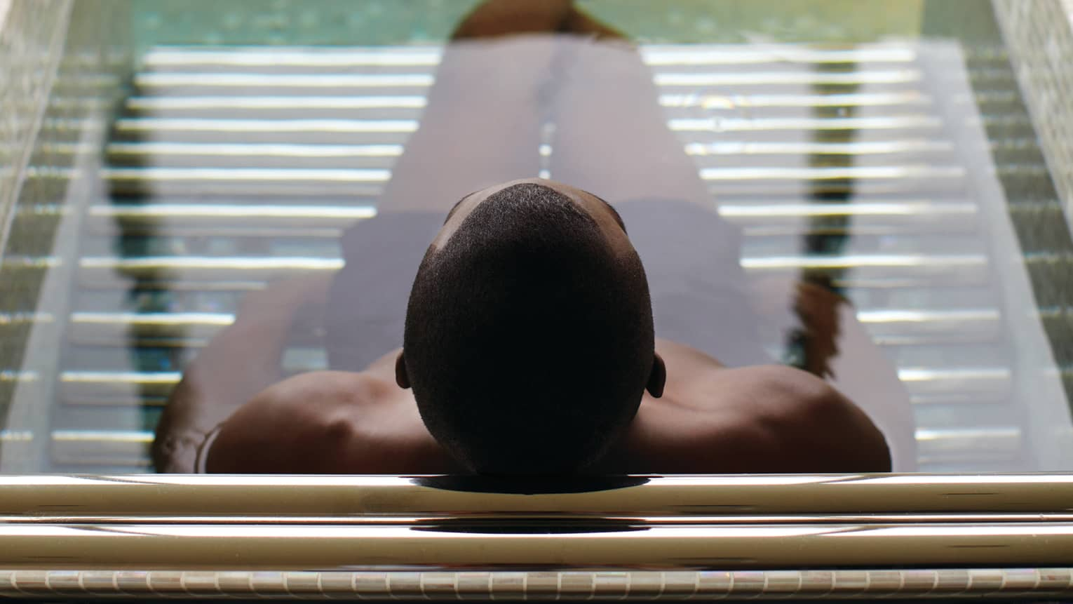 Silhouette of back of man's head, legs in spa tub