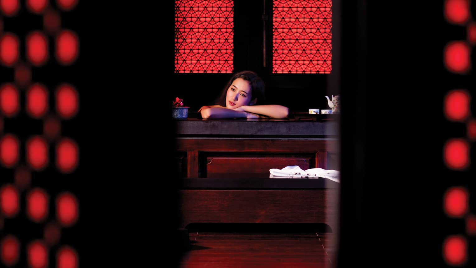 Woman rests head on crossed arms on table in dark red-and-black spa