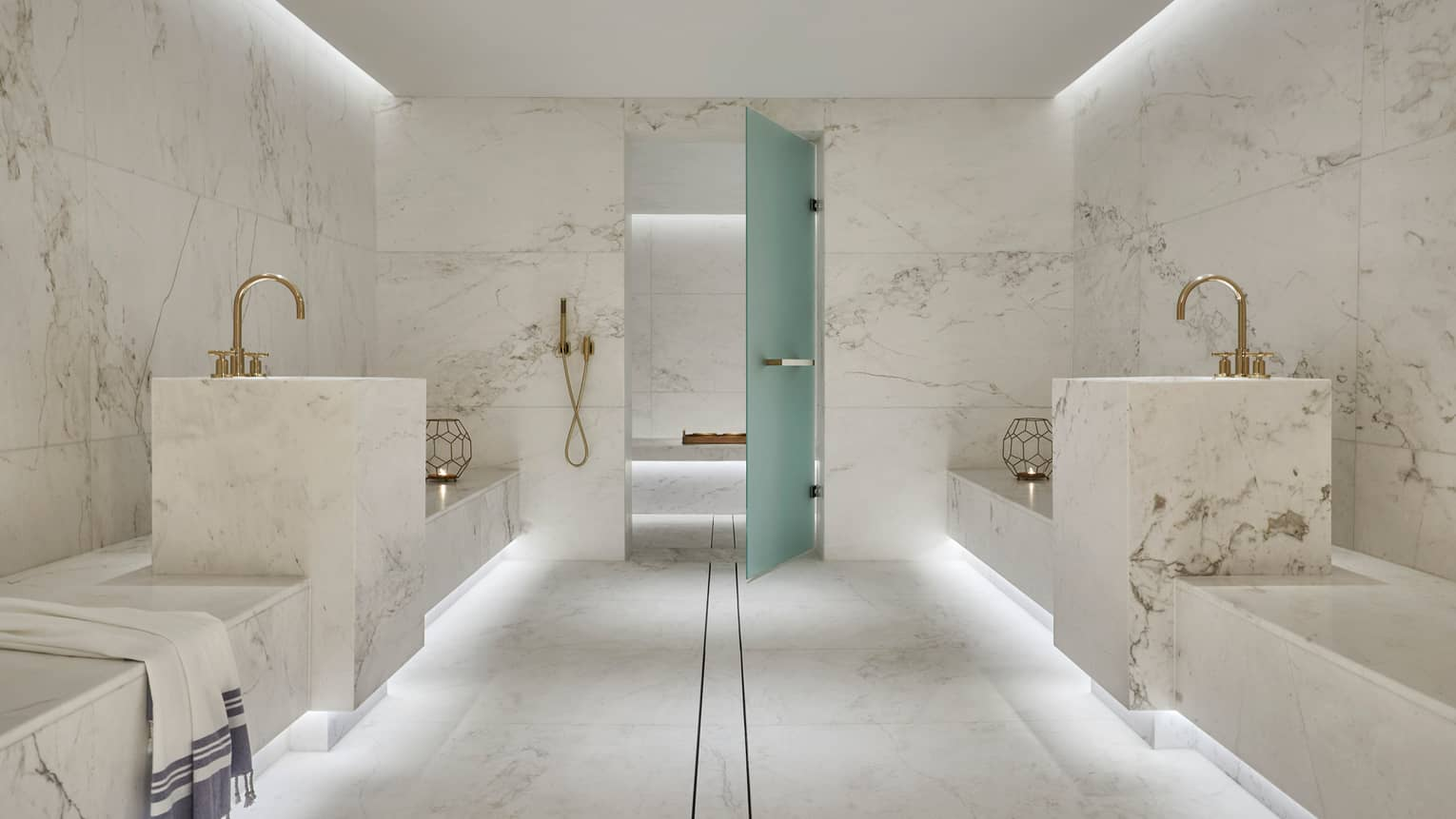 Tropical Hammam escape in white marble spa room, towel draped over side