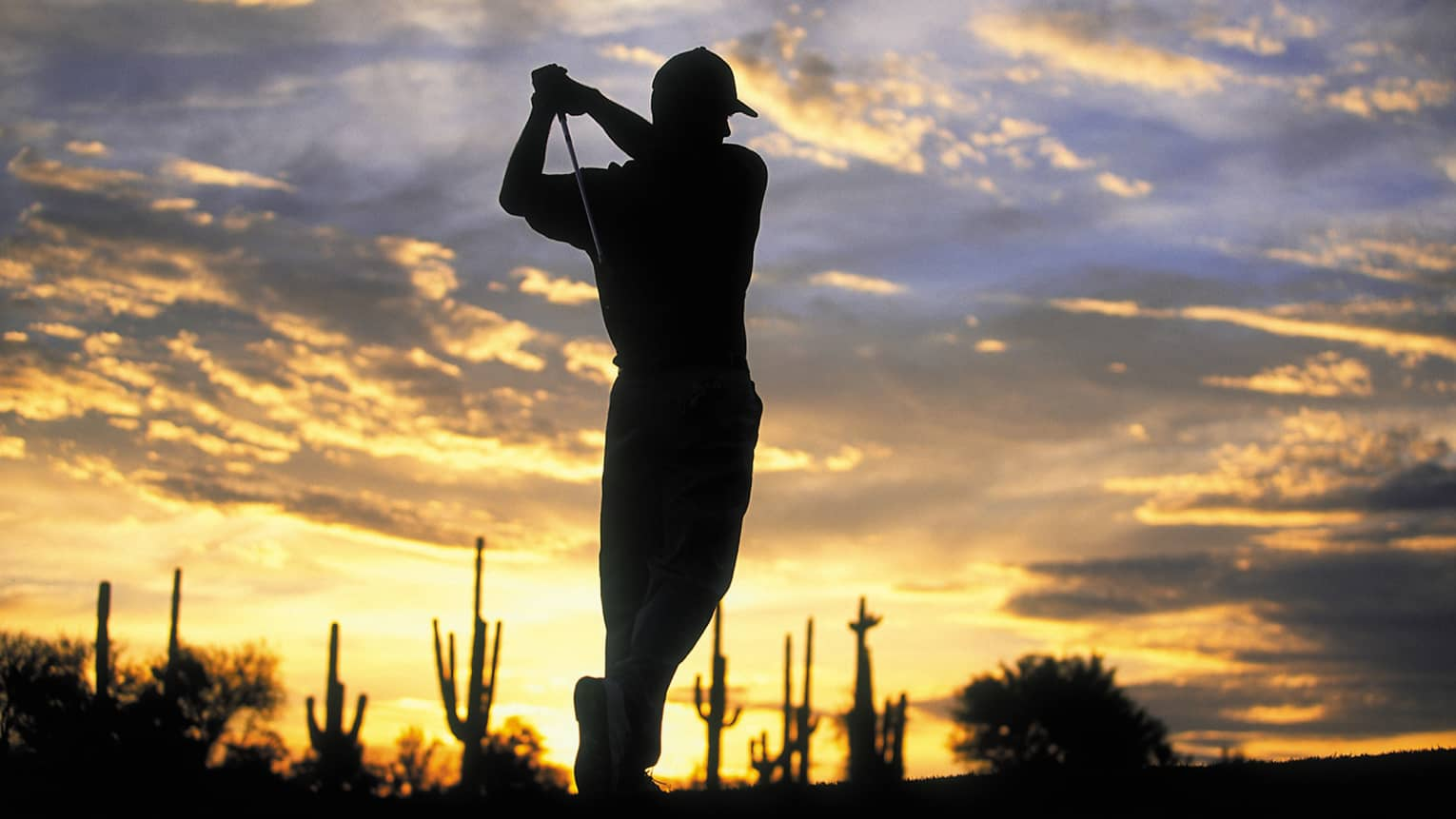 Silhouette of golfer swinging club against sunset sky at Troon North golf course