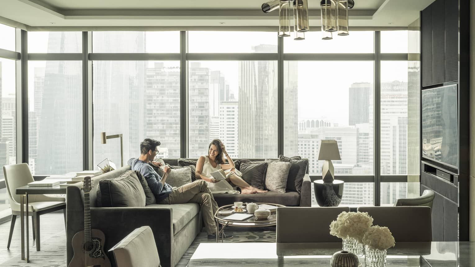 Couple relaxes on sofas in hotel suite with bright floor to ceiling windows