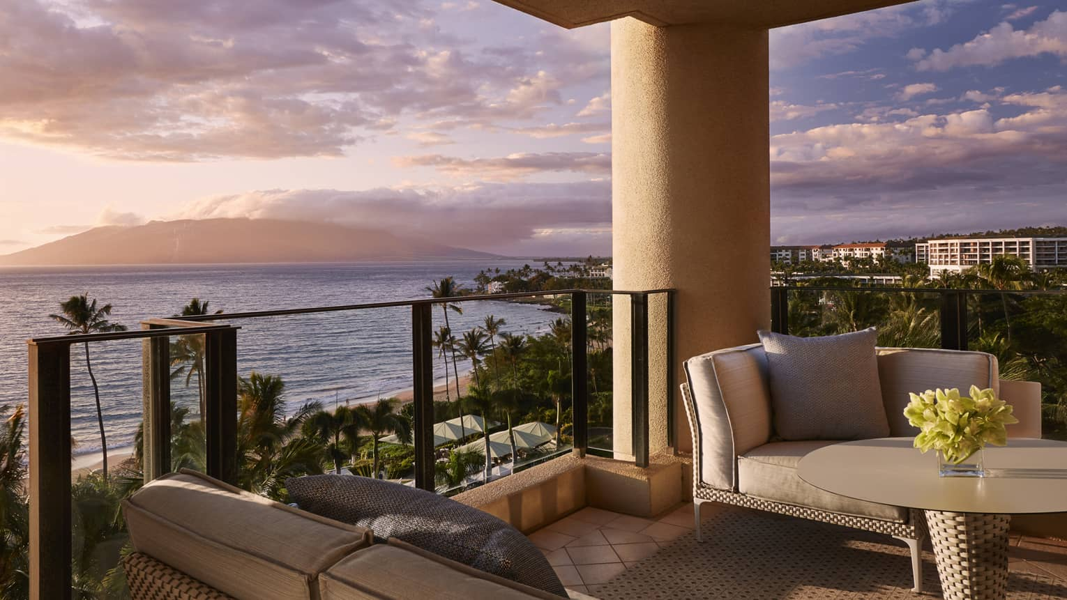 Balcony with wicker patio furniture, brown cushions in front of ocean view at sunset