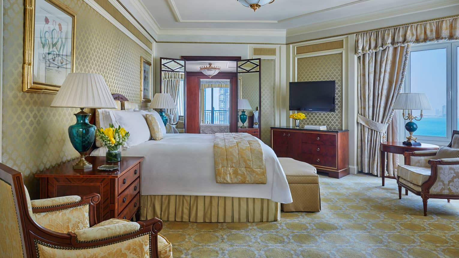 State Suite room with yellow and gold accents, window overlooking blue sea