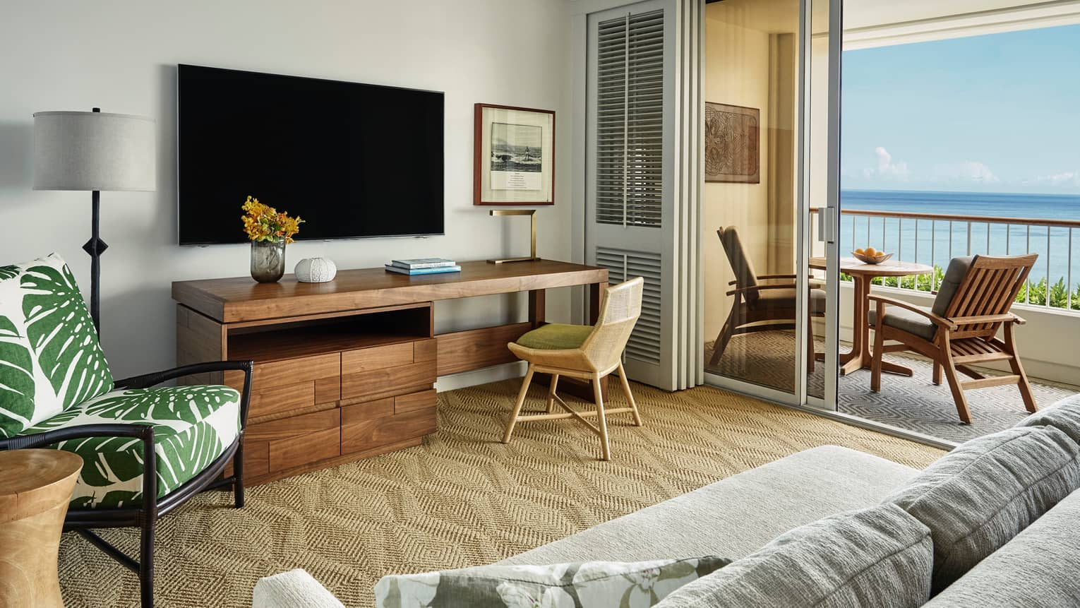 Oceanfront Suite large rustic wood desk under TV, palm print chair, open balcony doors