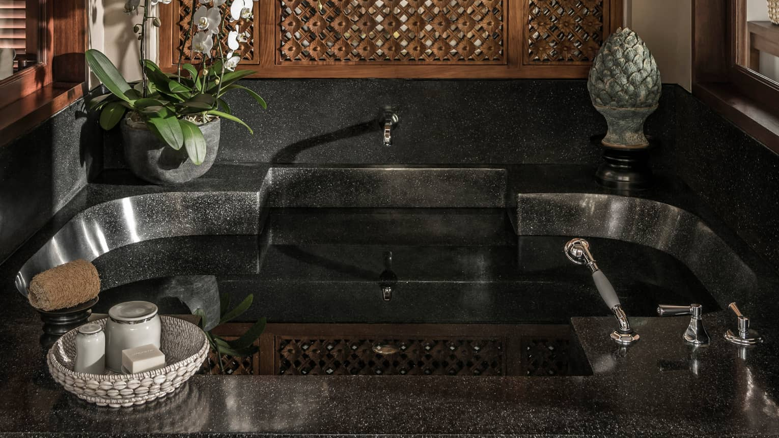 Black stone bathroom tub with potted plant and sculpture on ledge, basket with soaps and jars