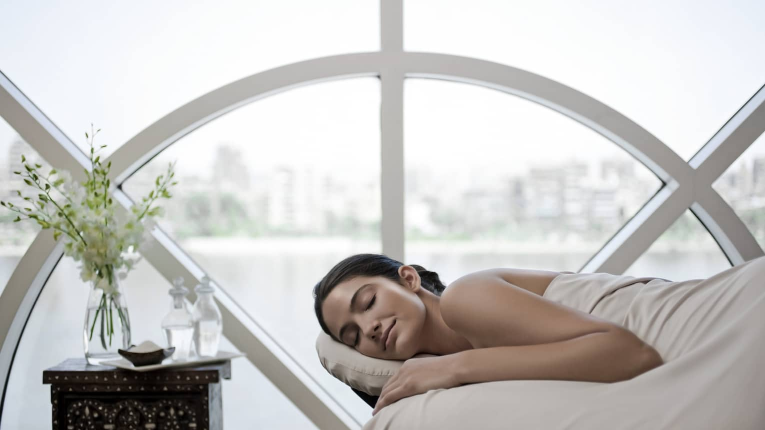 Woman with eyes closed, smile lies on massage bed in spa suite under white sheet in front of large sunny window