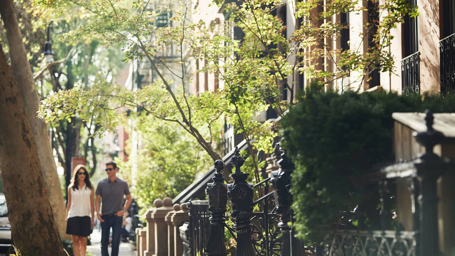 Man and woman hold hands, walk down New York residential sidewalk past iron posts