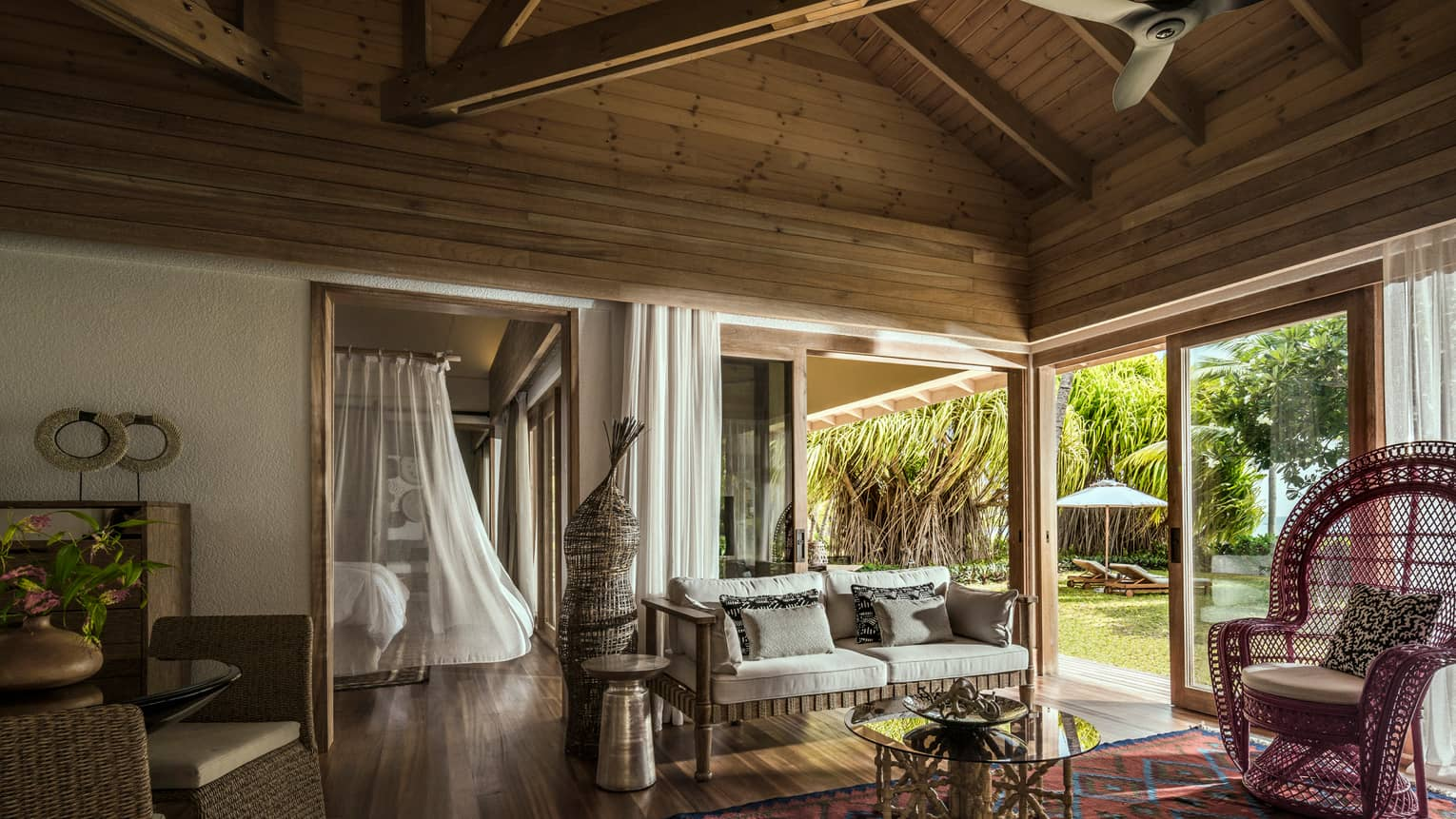 One-bedroom suite living room wicker furniture under wood beam roof, bed with white sheer canopy