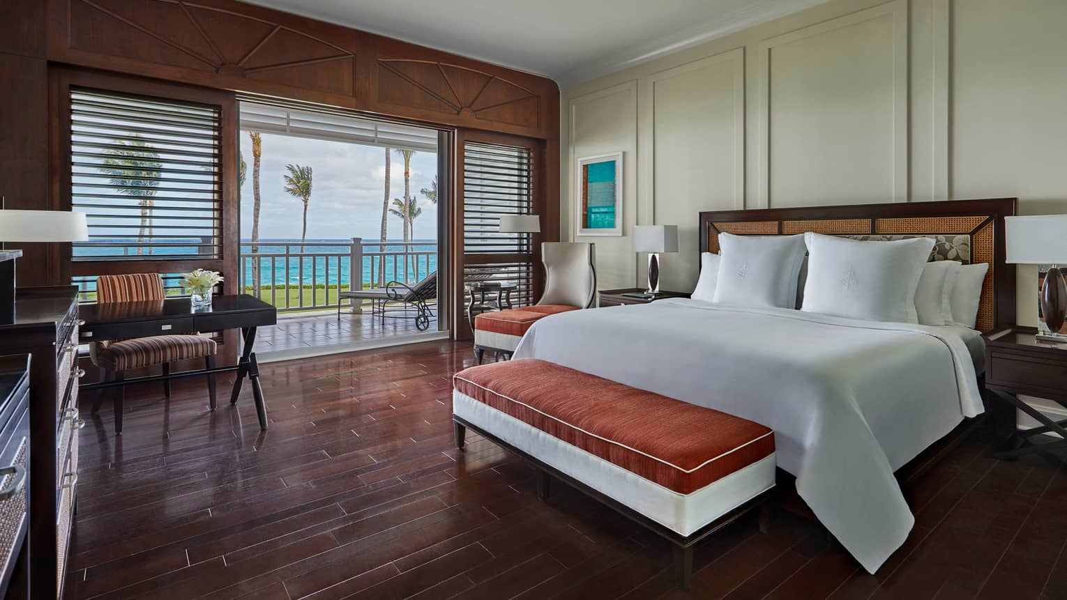 Luxury Beachfront Ocean Room bed, padded bench, desk by patio window, wood shutters