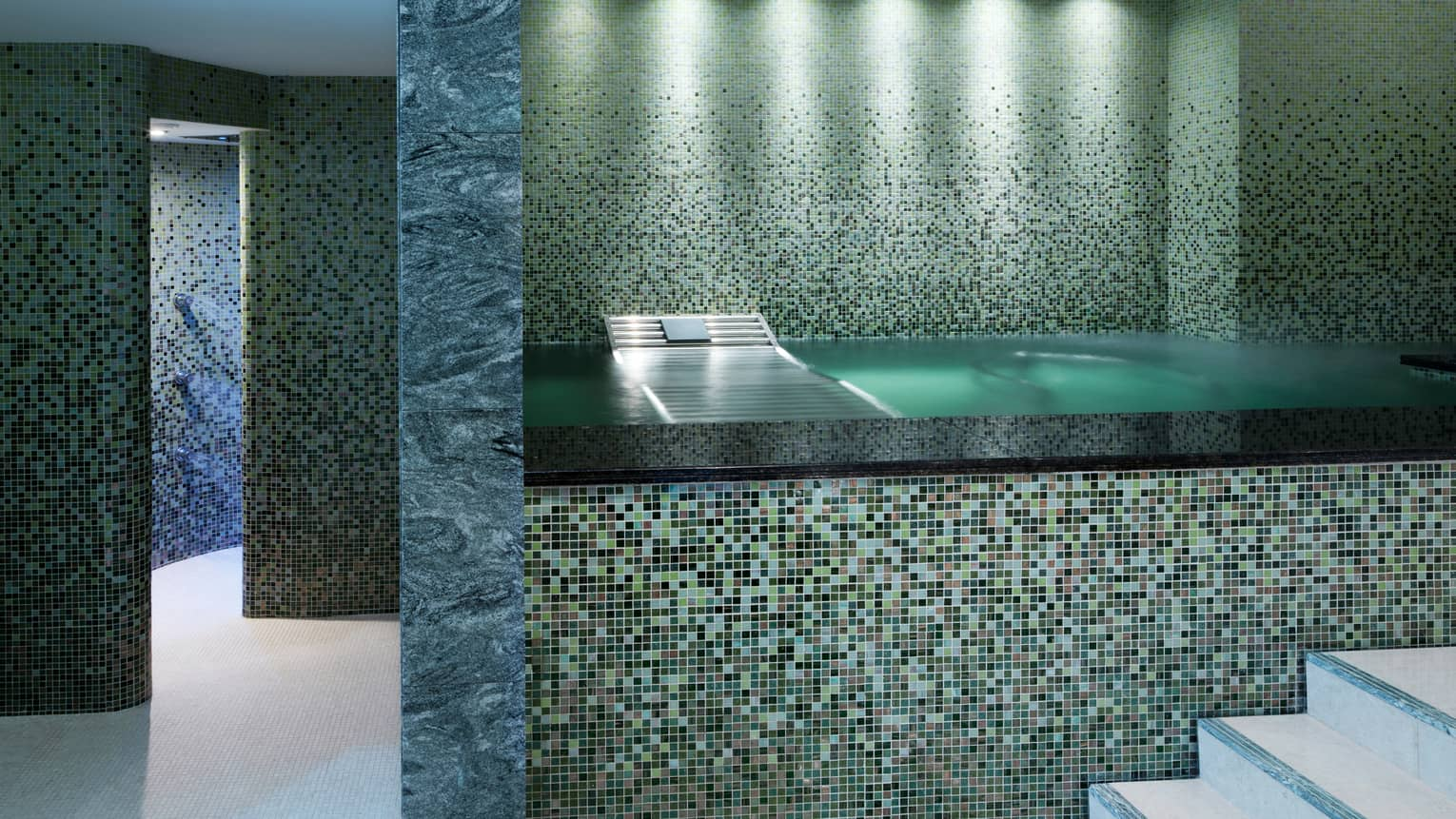 Raised bath with elaborate tile design in marble-and-tile spa room