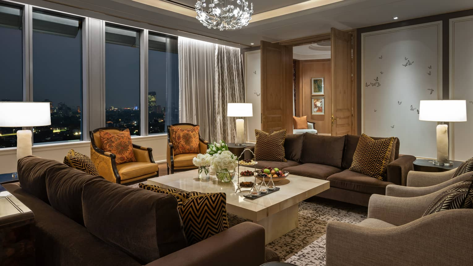 Ambassador suite living room with two couches, four armchairs, brown & gold accents, floor-to-ceiling windows