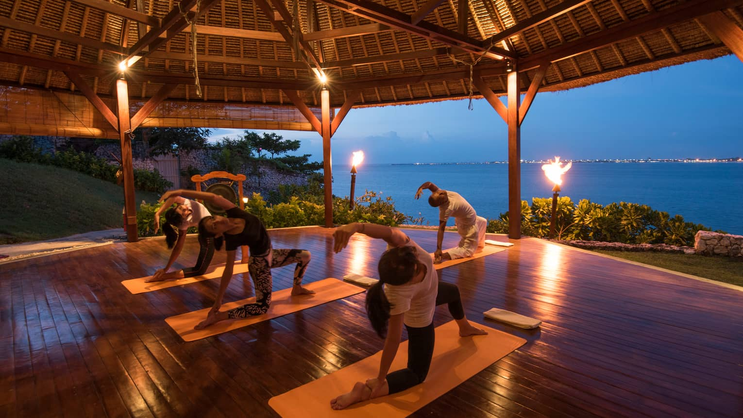 Four people outstretched in yoga pose on mats in torch-lit gazebo for Night Fire Yoga class