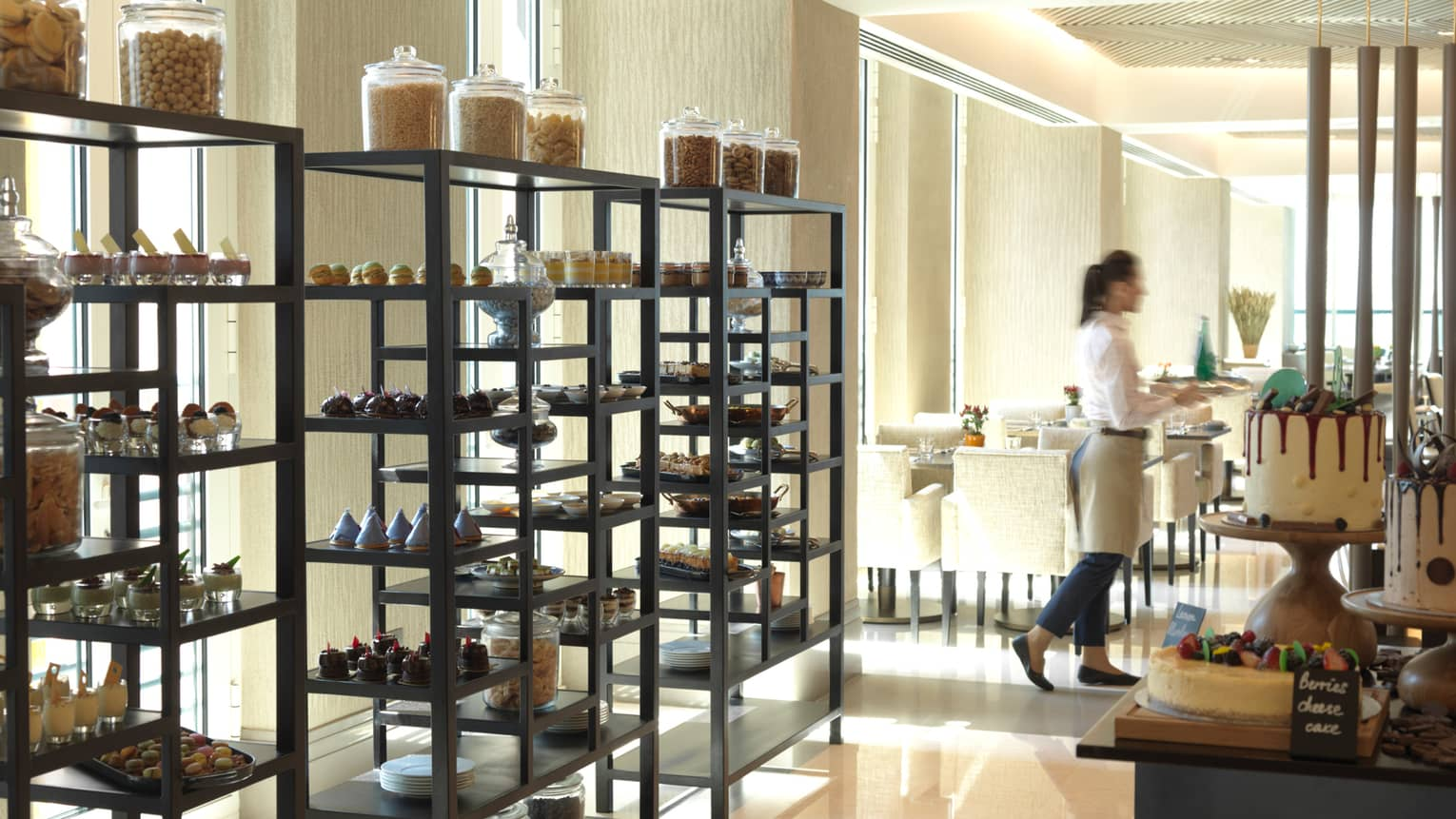Three tall racks filled with fancy pastries and desserts in front of window, server carries tray to dining room