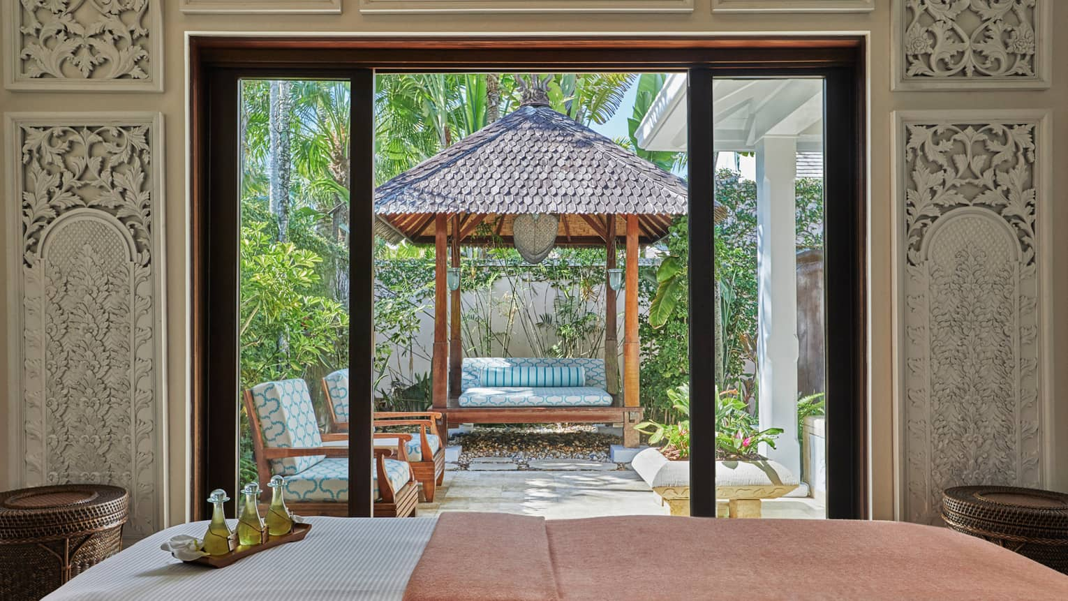 Bali-inspired spa treatment bed by open door to patio lounge