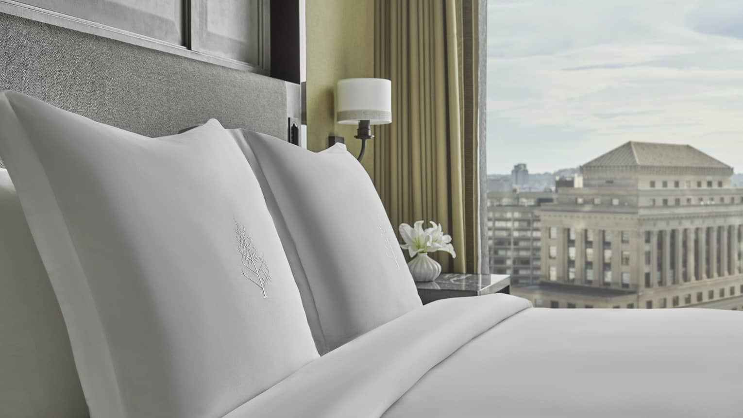 The bed is made with white linens in the Executive Suite