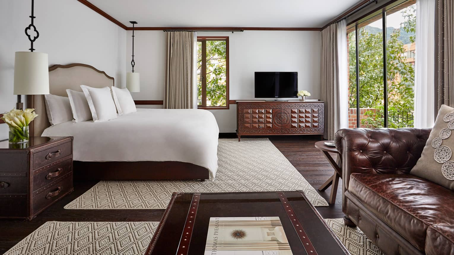 Executive Suite with bed with white linens, wood trunk-style coffee table and nightstand, large glass patio door