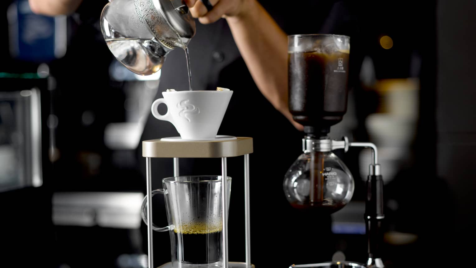 Server pouring hot water into white ceramic coffee filter above glass mug