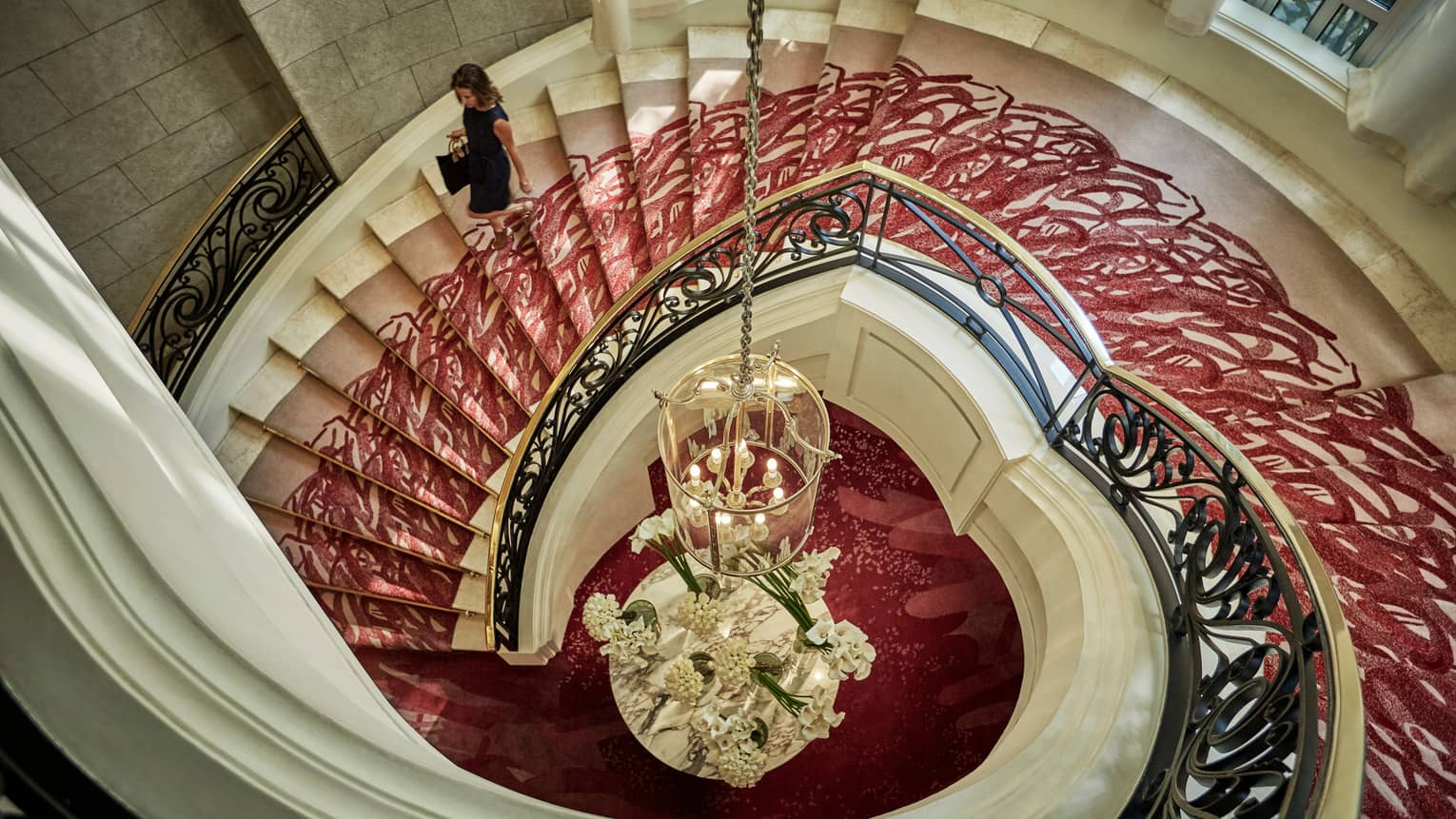 Aerial view of woman walking down white spiral staircase with red carpet, gold railing